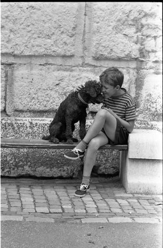 Enfant jouant avec un chien devant la tour Baudet