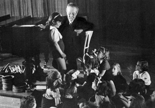 Emile Jaques-Dalcroze au piano entouré d'enfants dont sa petite-fille (vers 1950)