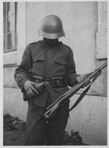 Genève, soldat montrant son arme brisée aux lendemains des événements du 09.11.1932