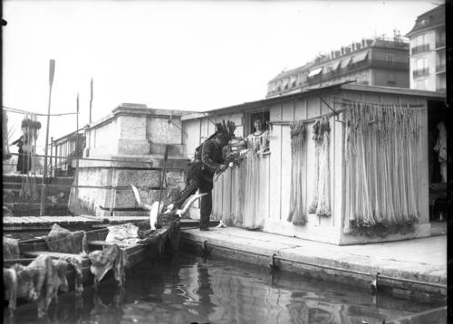 Genève, quai Wilson: homme habillé en Indien offre des fleurs à une femme se trouvant dans une cabane de pêcheur