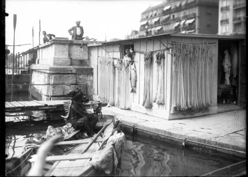 Genève, quai Wilson: homme habillé en Indien assis dans une barque devant une cabane de pêcheur